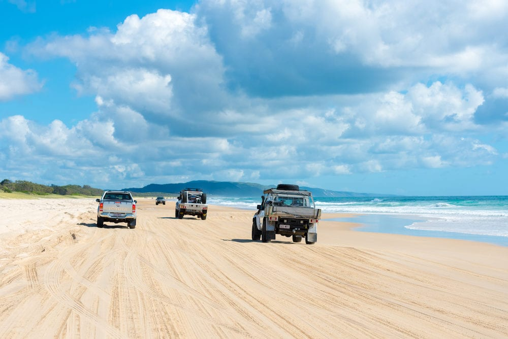 Rainbow Beach, QLD, Australia- 4wd vehicles at Rainbow Beach, a popular tourist destination and a gateway to Fraser Island, its name derives from the rainbow-coloured sand dunes.