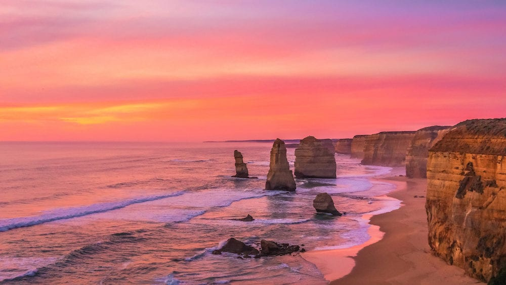 Twelve Apostles along the Great Ocean Road in Australia bathed in pink light during sunset golden hour