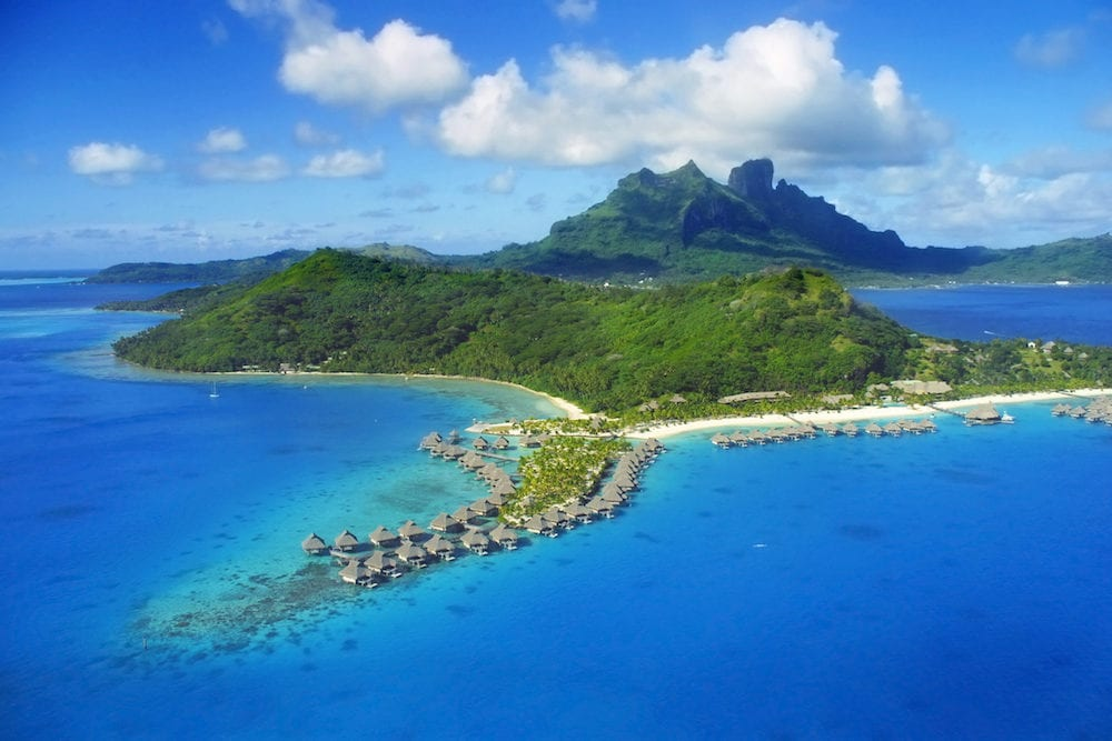 Aerial View of Bora Bora with Mount Otemanu in background and coral reef.