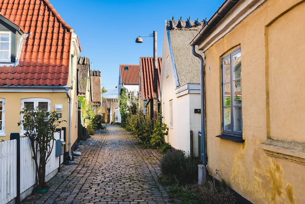 Old narrow street in Dragor Denmark - fishing village near Copenhagen. Traditional scandinavian houses cobblestone and green ivy.