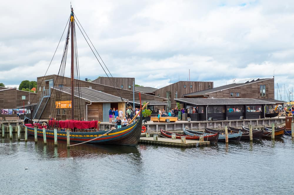 Roskilde Denmark - : Replicas of ancient boats and visitors outside the Viking Ship Museum