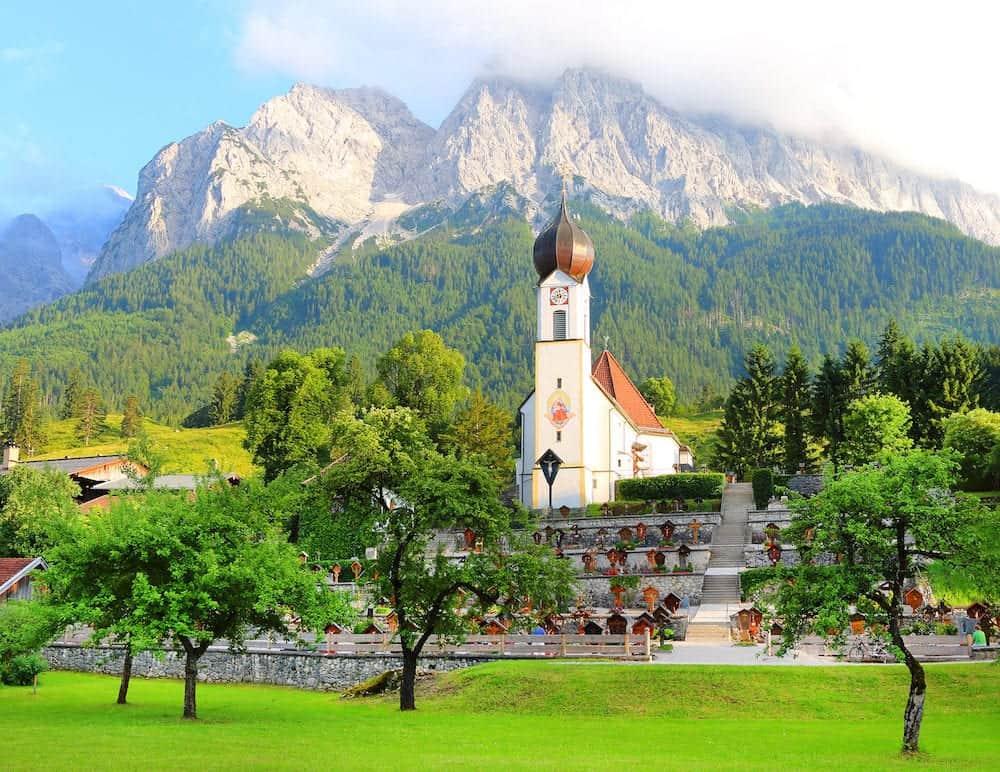 GARMISCH-PARTENKIRCHEN / GERMANY - : View of Grainau's church with the Zugspitze behind. It is Germany's highest peak (2962 m).