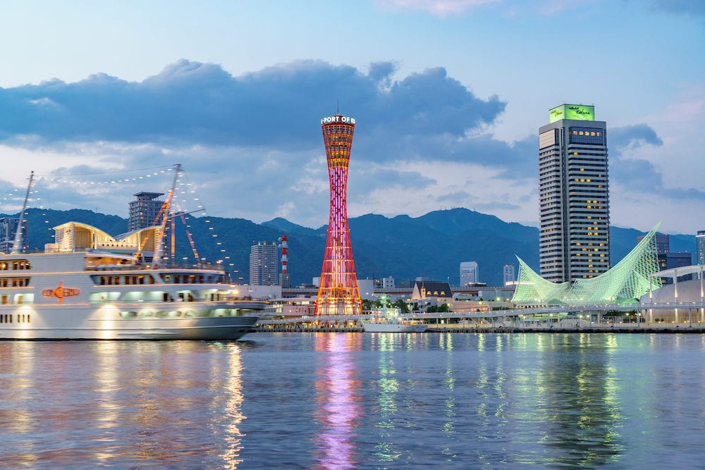 KOBE, JAPAN - Kobe tower and Okura Hotel at dusk in the Port of Kobe in Kobe, Japan.