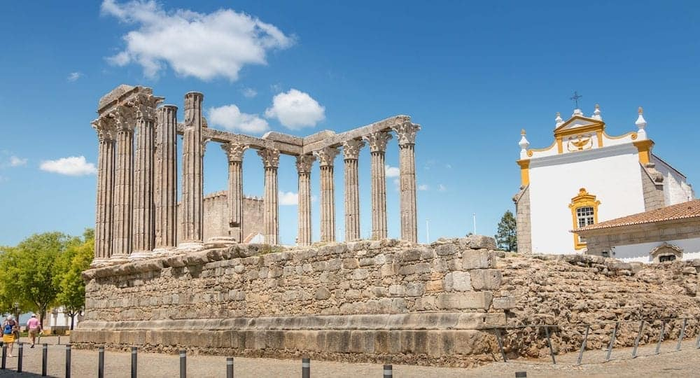 Evora, Portugal -: architectural detail of the Roman temple of Evora in Portugal or Temple of Diana in front of which people are walking on a spring day. It is a UNESCO World Heritage Site