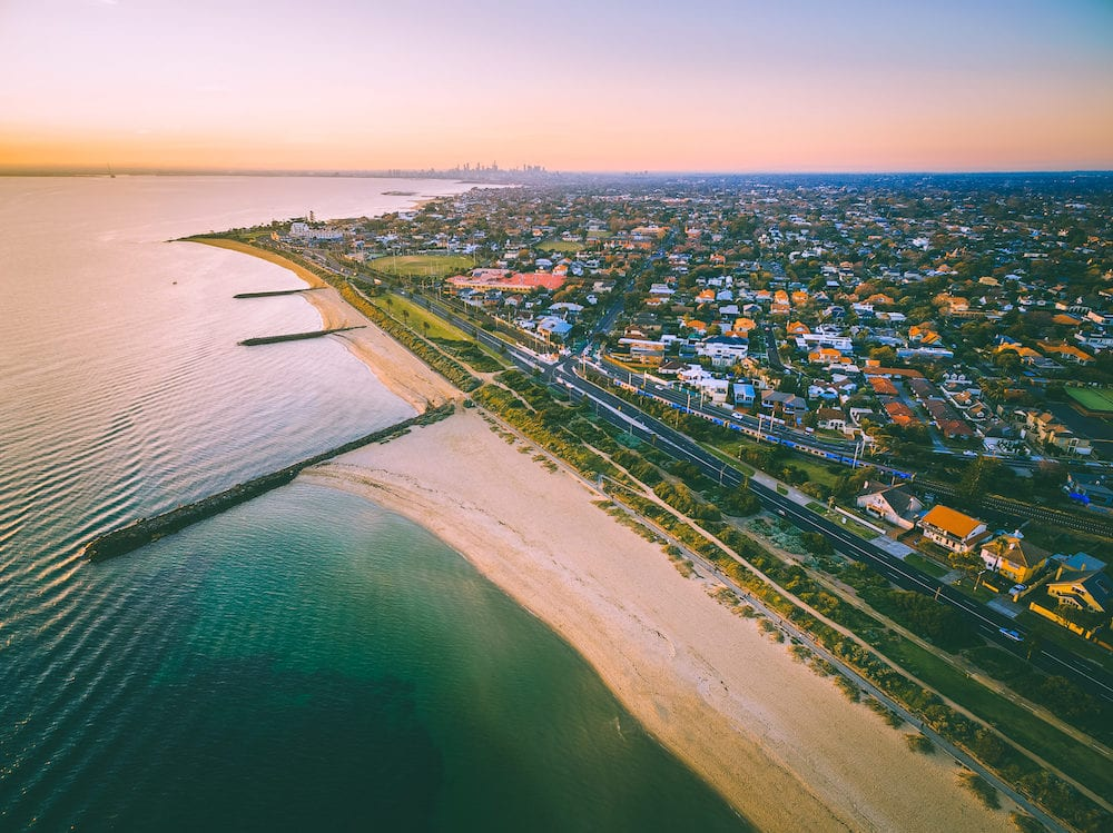Aerial view of Port Phillip Bay and Melbourne coastline suburban living quarters at dusk with Melbourne CBD skyscrapers in the distance