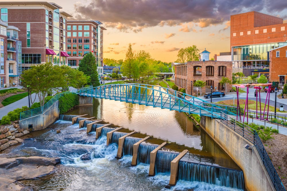 Greenville, South Carolina, USA downtown cityscape on the Reedy River at dusk.