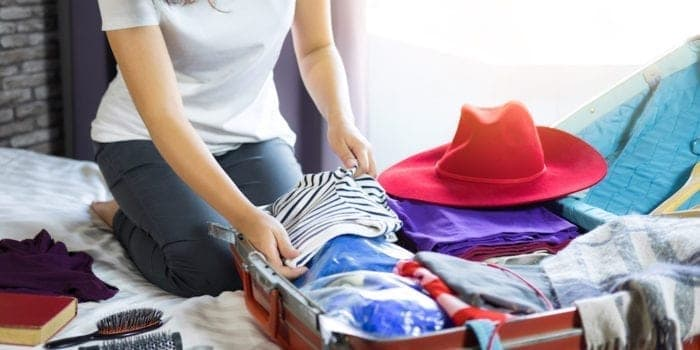 Travel and vacation concept, happiness woman packing stuff and a lot of clothes into suitcase on bed prepare for her travel and journey trip.