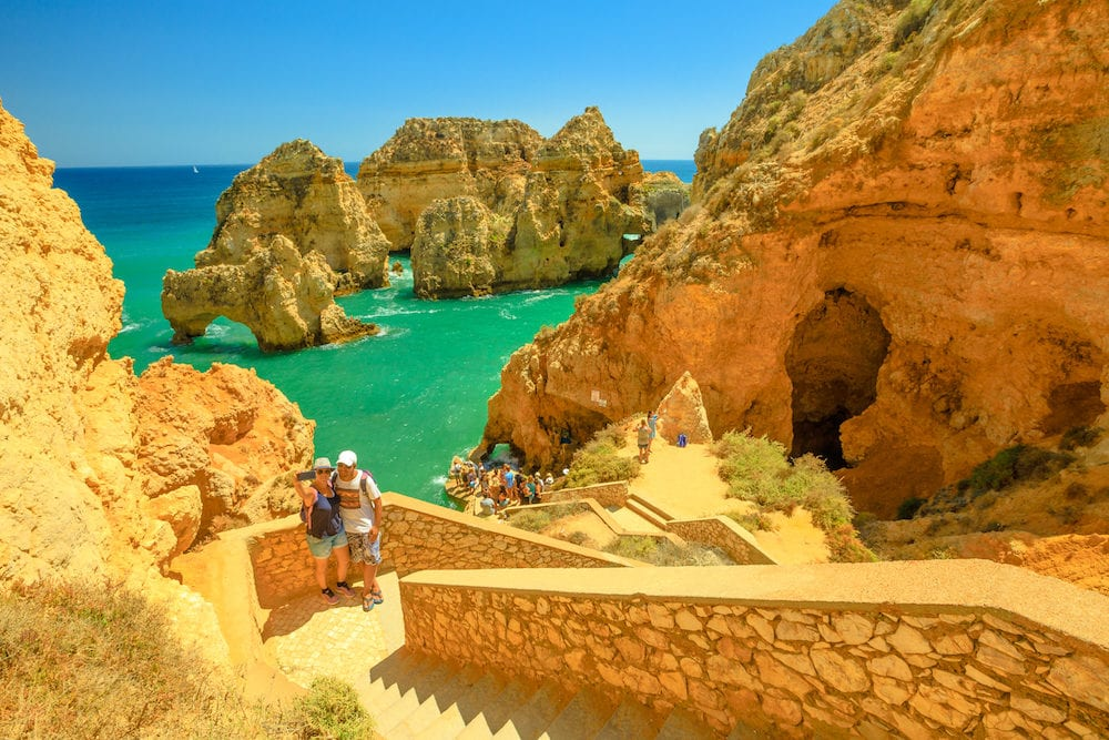 Lagos, Portugal - couples take selfie on the steps leading down to the caves at Ponta da Piedade in Lagos, one of the main tourist destinations in Algarve Coast, Portugal. Sunny day.