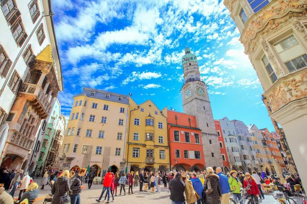 NNSBRUCK AUSTRIA - - People in Innsbruck city center under Stadtturm tower. It is capital city of Tyrol in western Austria Europe.