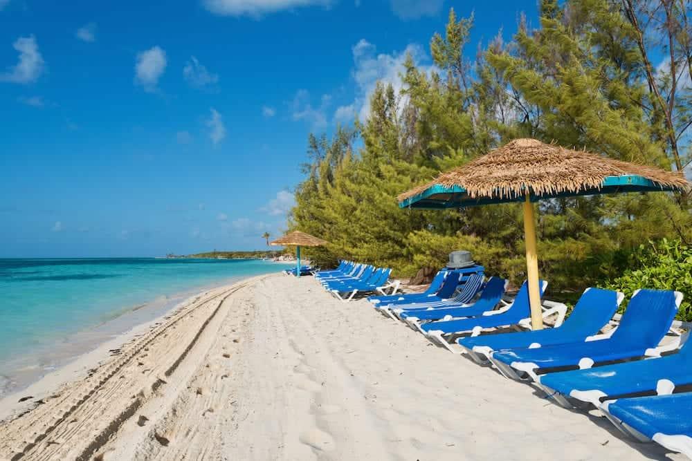 Lounge chairs on a white sand beach Coco Cay Bahamas