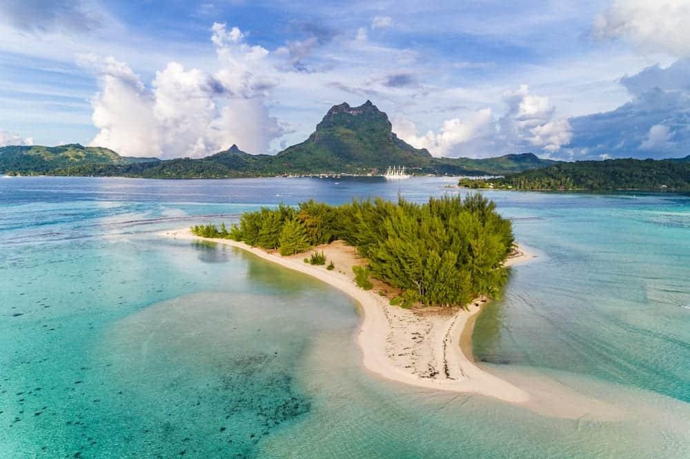 Bora Bora aerial view of luxury travel cruise ship vacation destination. Drone shot above motu paradise island r in lagoon and Mt Pahia, Mount Otemanu, Tahiti, French Polynesia, South Pacific Ocean.