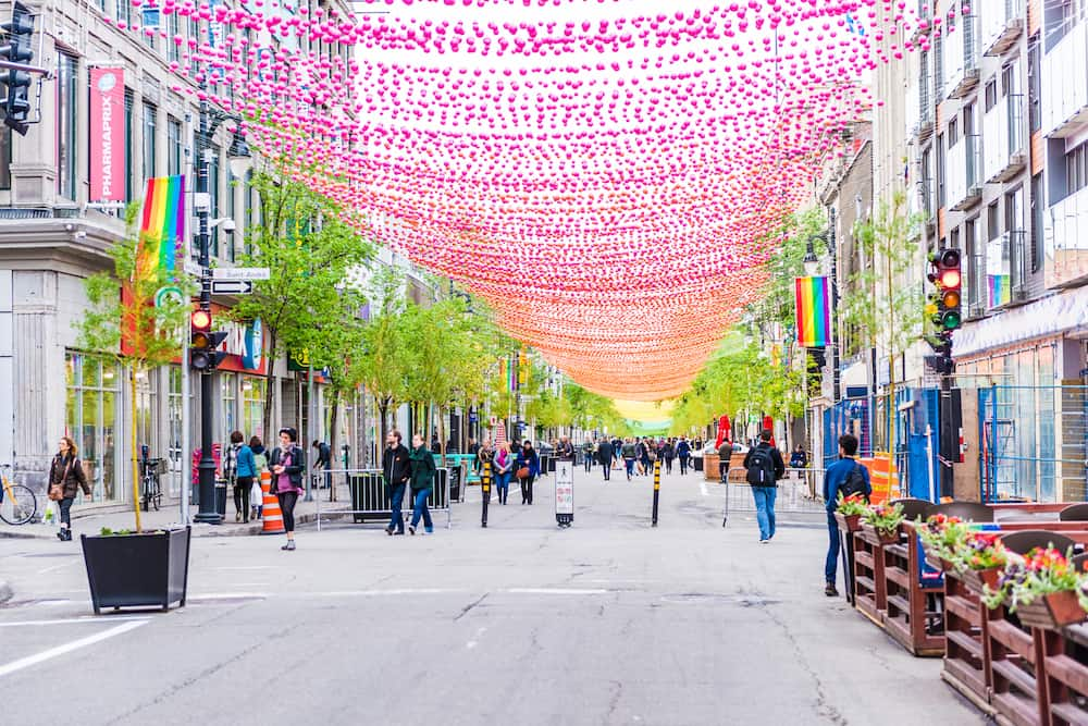 Montreal Canada - People walking on Sainte Catherine street in Montreal's Gay Village in Quebec region with hanging decorations