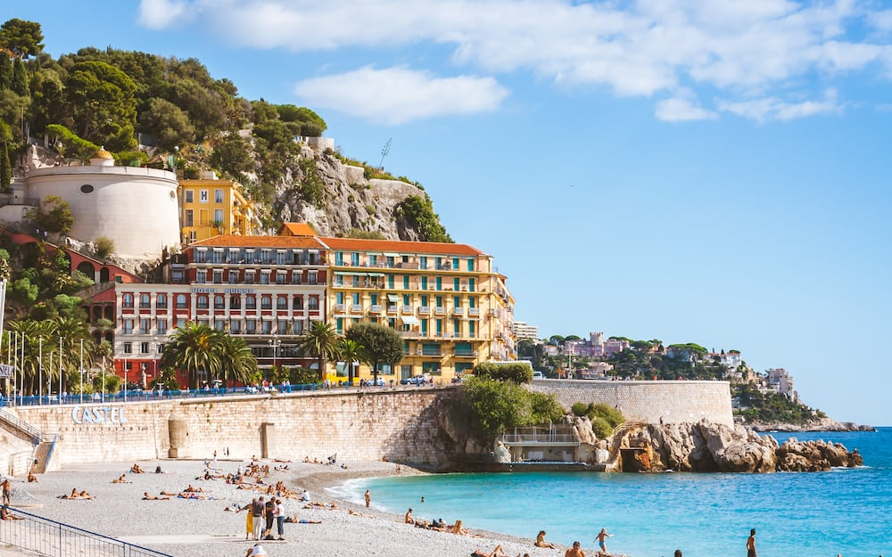 NICE, FRANCE -Beautiful nicoise architecture and people relaxing on beach that stretches along Promenade des Anglais in Nice