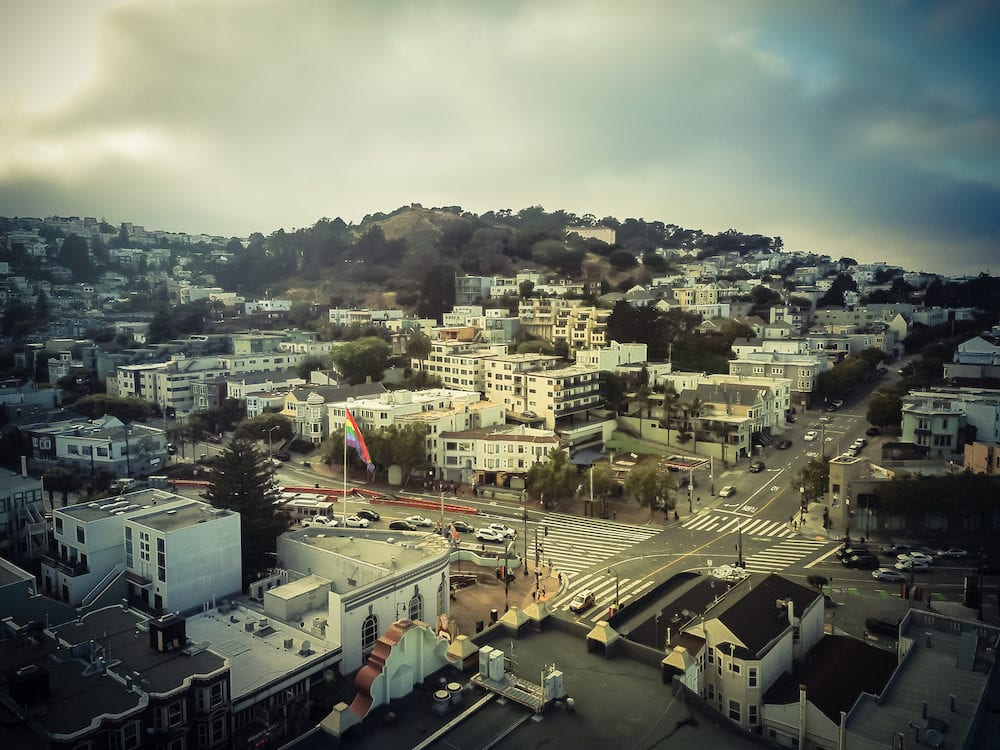 Aerial view Castro District in Eureka Valley neighborhood flying LGBT pride flag near street intersection. Famous town in San Francisco, California, synonymous gay culture, historic Victorian houses