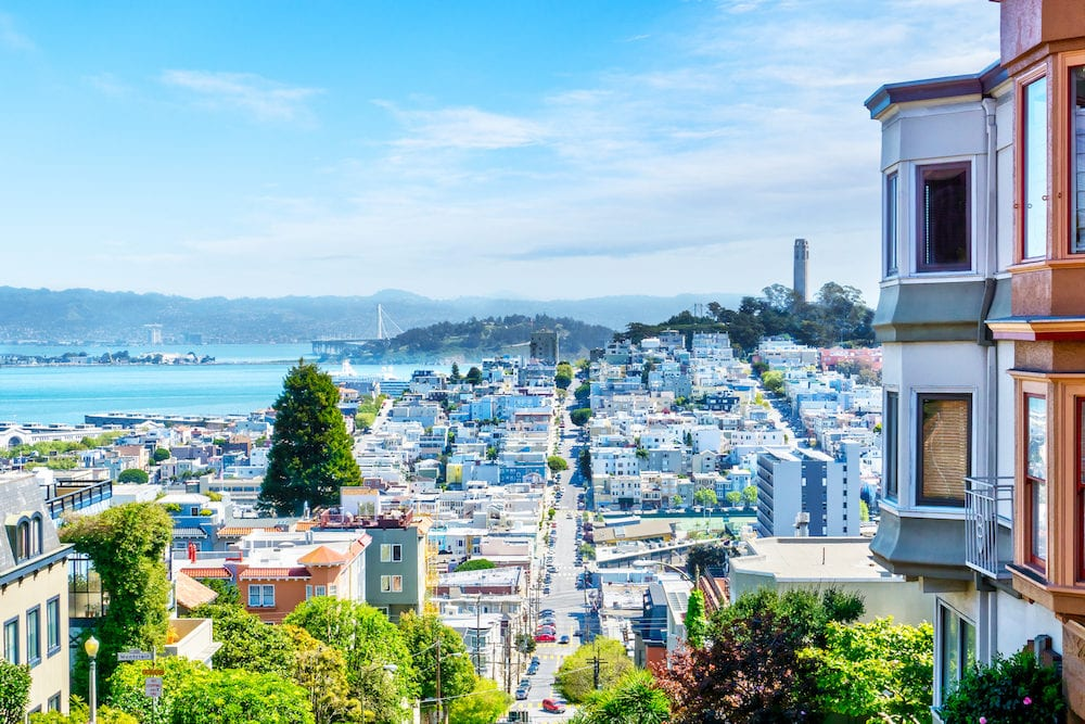 High-angle view of San Francisco skyline at Lombard Street toward San Francisco Bay in downtown North Beach community showing Fisherman's Wharf and Coit Tower.
