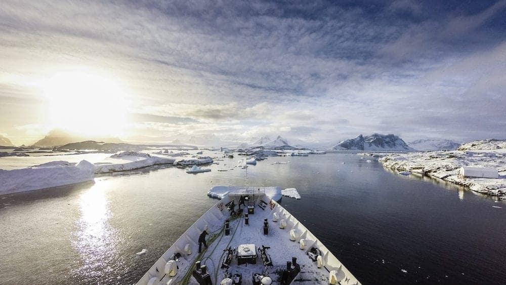 Ship cruising among icebergs between frozen land of Antarctica and islands surrounding it