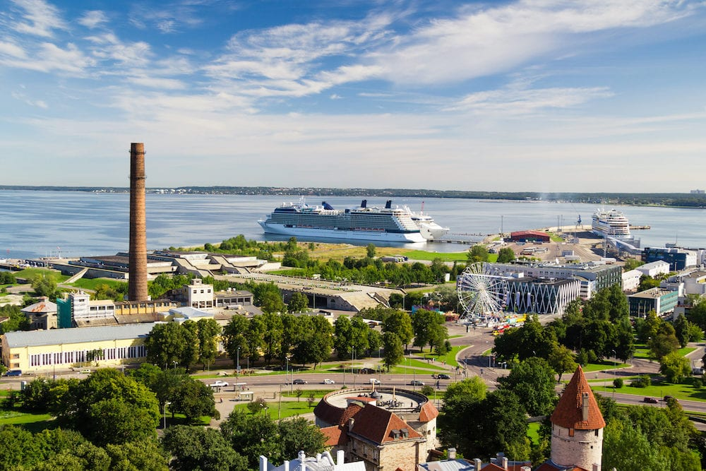 Summer city landscape with seaport, cruise ships and part of fortress in the Old Town in Tallinn, Estonia. Panorama with green trees and Baltic sea on background. Cloudy blue sky.