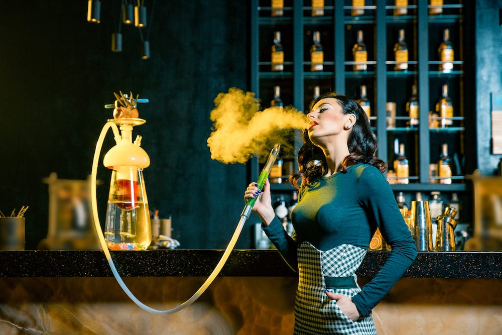 Young brunette woman smoking a hookah behind the bar. Cloud of smoke. Beauty portrait of young woman enjoying the hookah