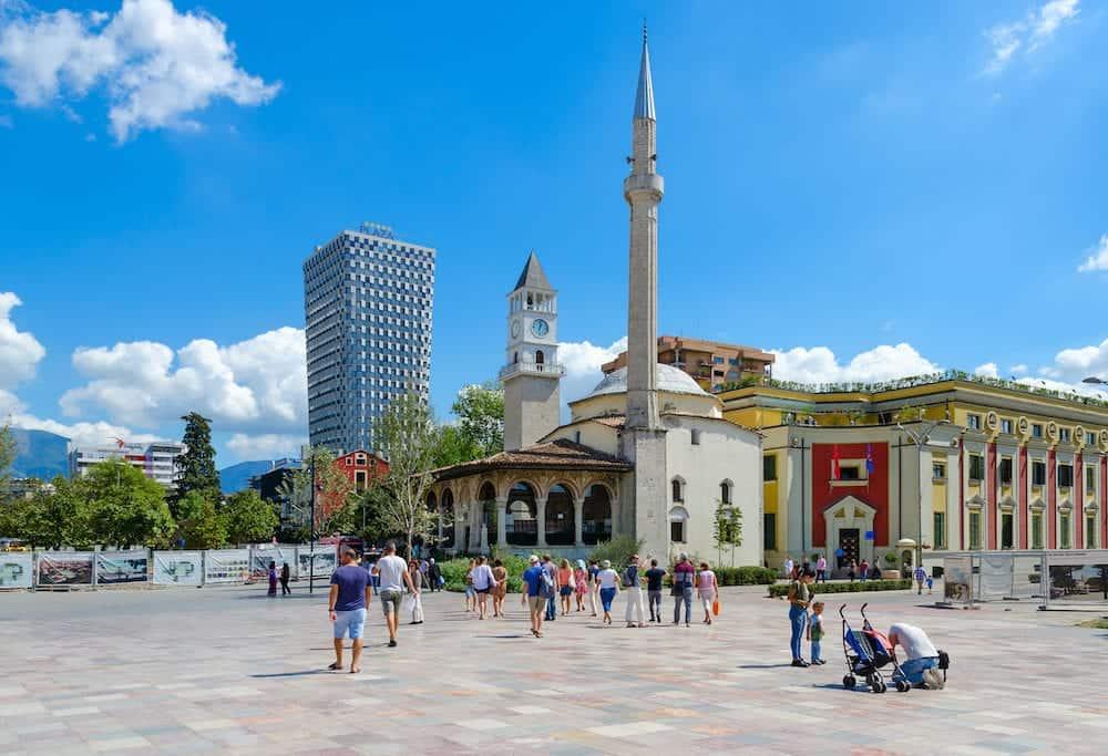 TIRANA ALBANIA - Group of unknown tourists on Skanderbeg Square. Efem Bay Mosque Clock Tower Plaza Hotel Tirana Albania