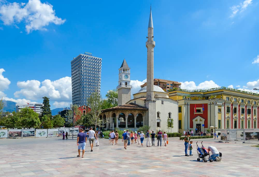 TIRANA ALBANIA - Group of unknown tourists on Skanderbeg Square. Efem Bay Mosque Clock Tower Plaza Hotel Tirana Albania