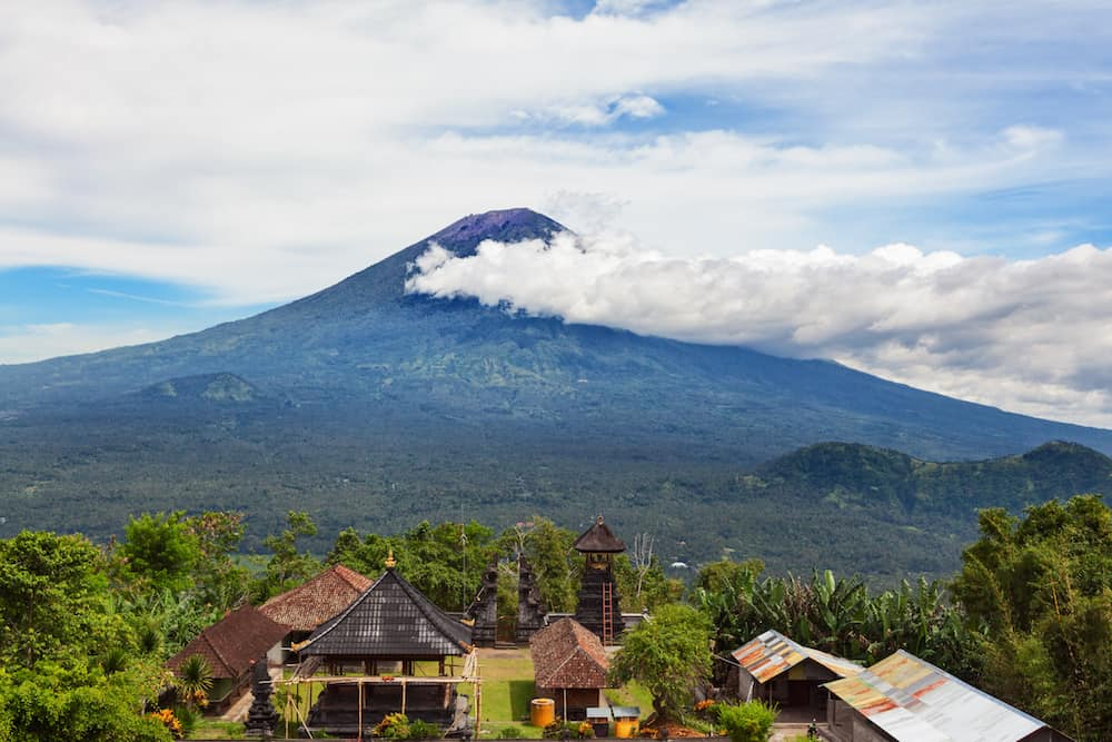 View from Lempuyang mountain to traditional Balinese temple on Mount Agung slopes background. Mount Agung is popular tourist hiking route and highest active volcano on Bali island Indonesia.