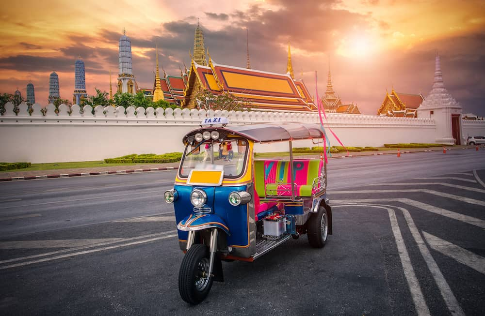 Tuk tuk on the background of Bangkok's Grand Palace Complex and Wat Phra Kaew, one of Bangkok's tourist attractions, Bangkok, Thailand