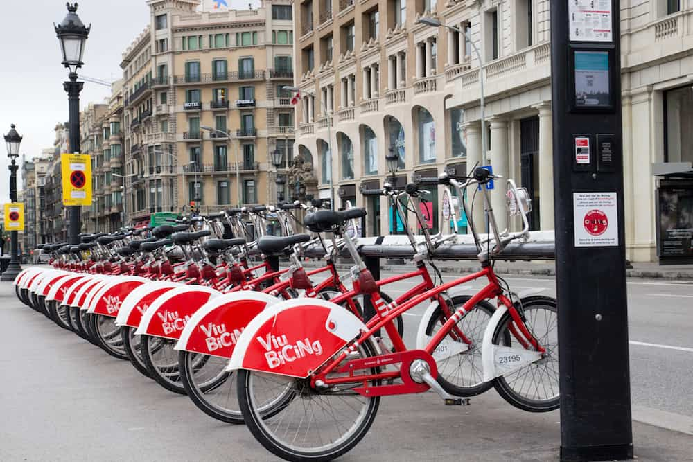 BARCELONA, SPAIN, Bicing bicycle rental station in Barcelona street, row of red and white bicycles in the background street and old vintage houses