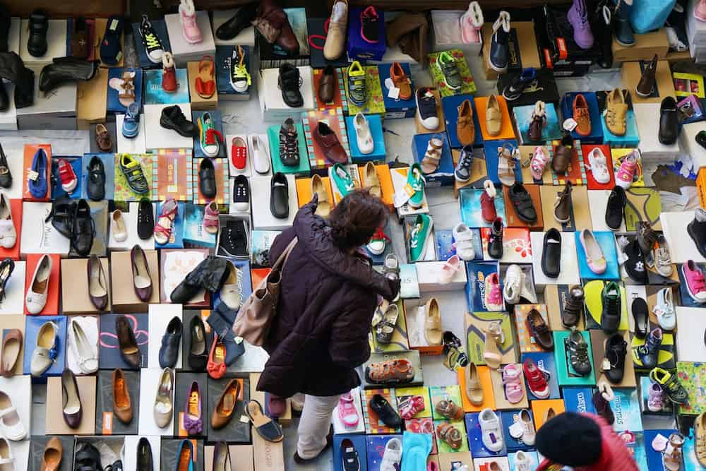 Barcelona, Spain - Woman browsing the large variety of shoes on offer at a flea market stall at Mercat dels Encants in Barcelona.