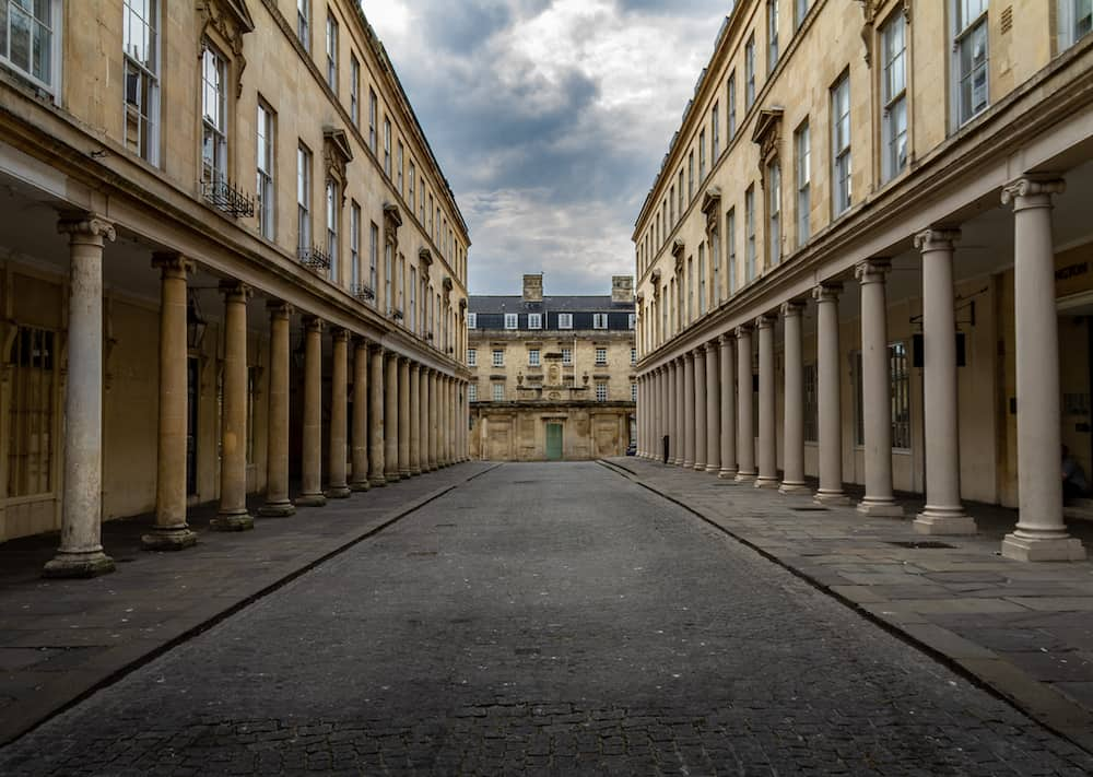 Gorgeous deserted street in Bath, England with Georgian columns on a cloudy day.