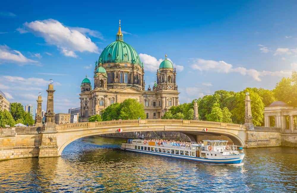 Beautiful view of historic Berlin Cathedral (Berliner Dom) at famous Museum Island with ship passing Friedrichsbrucke bridge on Spree river in golden evening light at sunset in summer Berlin Germany
