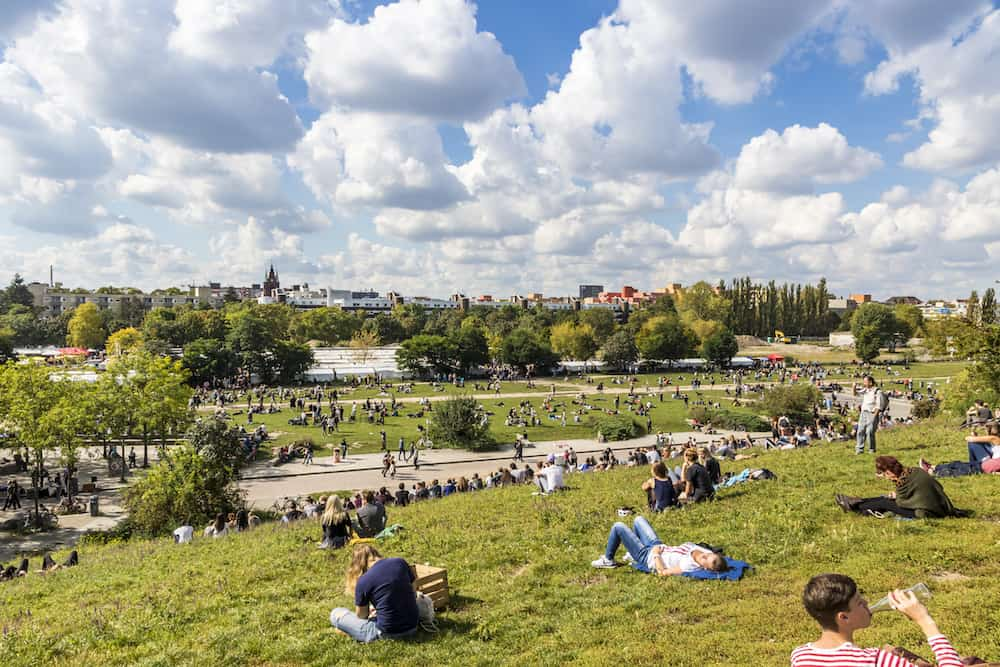 BERLIN GERMANY - People enjoy sunny Sunday at Mauerpark. Situated in death strip of Berlin Wall (Mauer) Mauerpark is now a social cultural and artistic center of Berlin