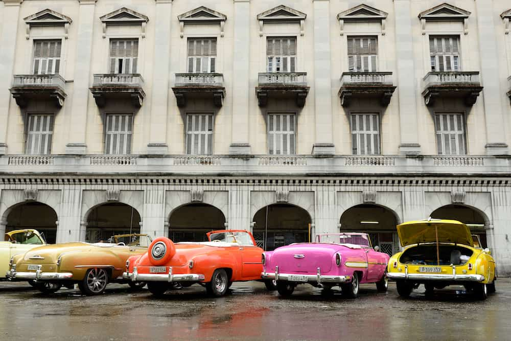 HAVANA, CUBA - : Old American colourful cars serving as taxis for tourists in order to go on a tour of old Havana standing in the Central Park in the heart of Havana