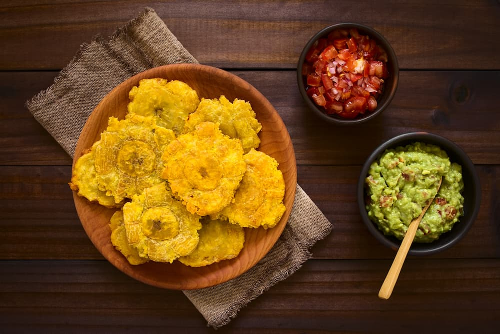 Patacon or toston fried and flattened pieces of green plantains a traditional snack or accompaniment in the Caribbean guacamole and tomato and onion salad on the side photographed overhead on dark wood with natural light