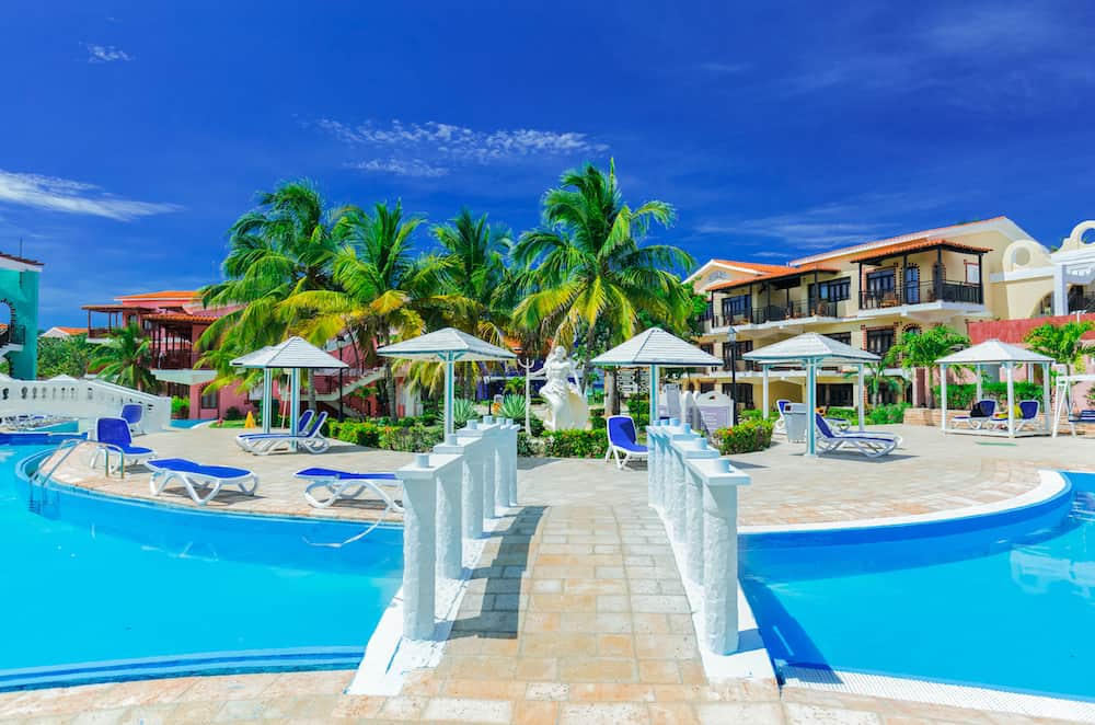Cayo Coco island, Cuba, Colonial hotel, stunning gorgeous view of Colonial hotel grounds, beautiful inviting swimming pool and retro stylish buildings on dark deep blue sky background