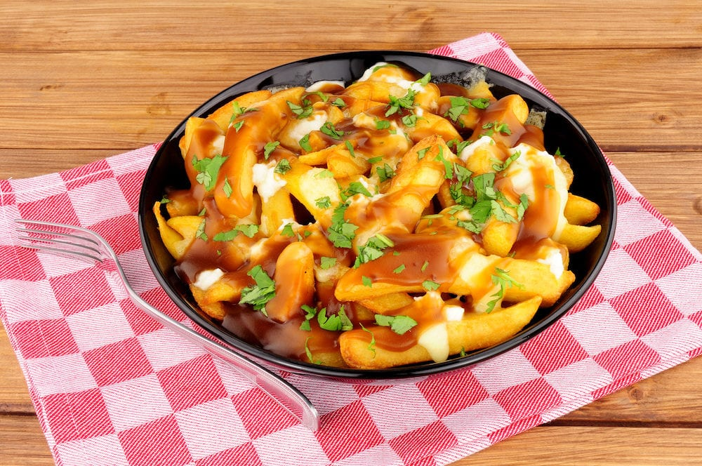 Bowl of traditional Canadian poutine meal on a wooden background