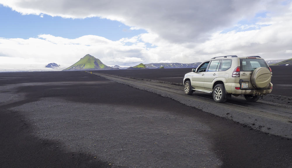 South Iceland, Nature reserve Fjallabak: Off road car Toyota Landcruiser driving on dirt mountain road F210 through black lava sand desert with green Maelifell mountain and myrdalsjokull glacier, blue sky white clouds