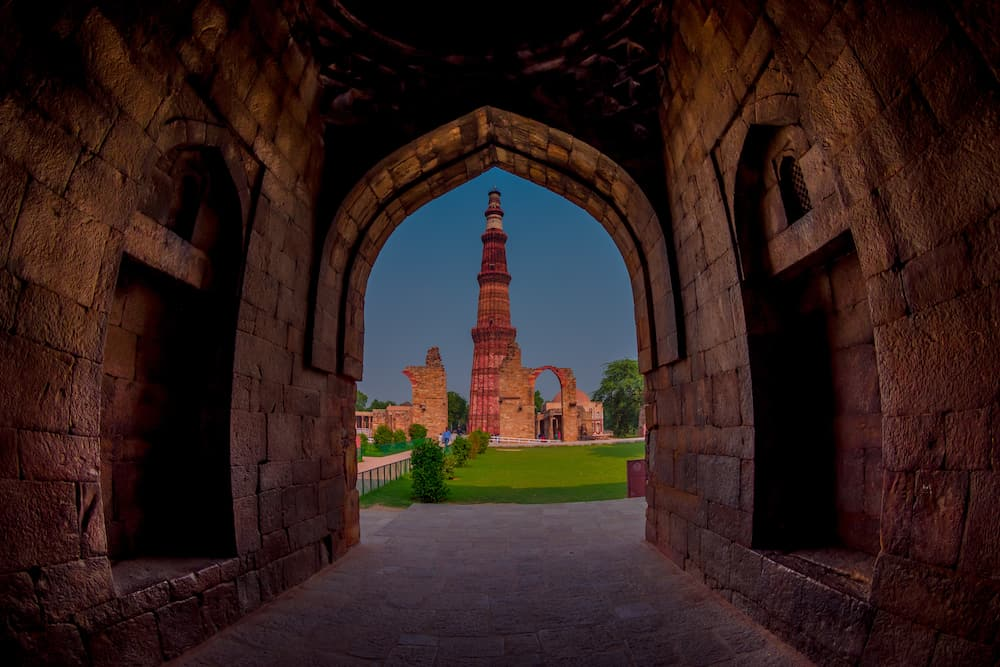 DELHI, INDIA - Beautiful view of Qutub Minar, through of a stoned arch, one of UNESCO world heritag site, built in the early 13th century located on south of Delhi, India.