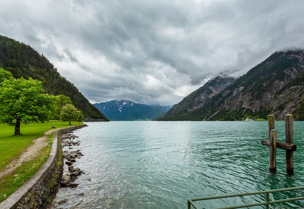 Achensee ( Lake Achen) summer landscape with green meadow and wooden moorage (Austria).
