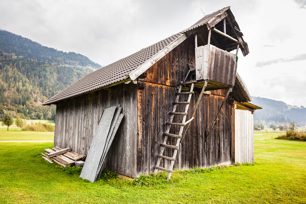 an old wooden barn in Austria on a green vibrant pasture