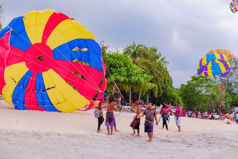 Langkawi, Malaysia - : A group of Malaysian people engaged in parachuting extreme sports on Pantai Tengah Beach, Langkawi island, Malaysia. Summer vacation and fun.