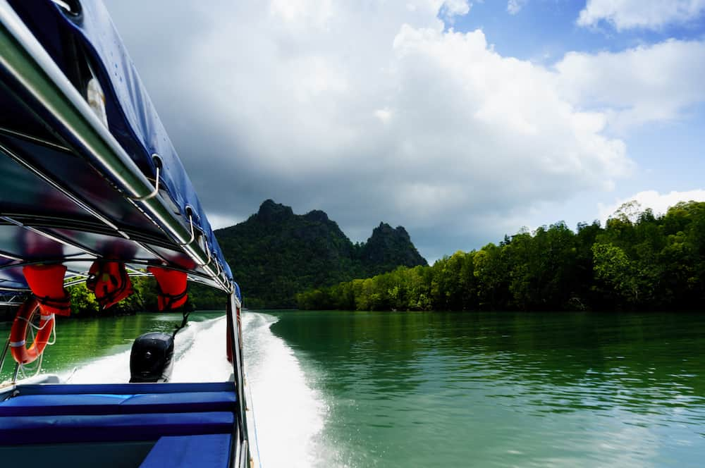 Boat moving at high speed on a beautiful river in Langkawi, shot from inside the boat. The seating, safety jackets and outboard motor are visible as are the beautiful tree covered hills, cloudy skies and blue water