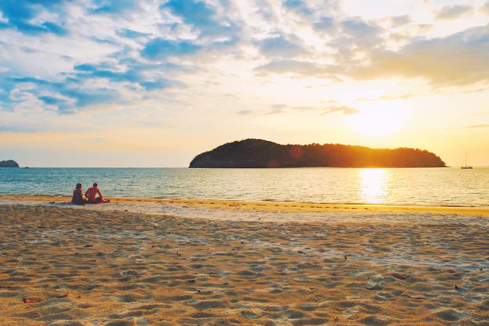 Pantai Tengah Beach at colorful sunset, Langkawi Island, Malaysia. Beach sunset is a golden sunset sky with a wave rolling to shore as the sun sets over the horizon. People relaxing on paradise beach