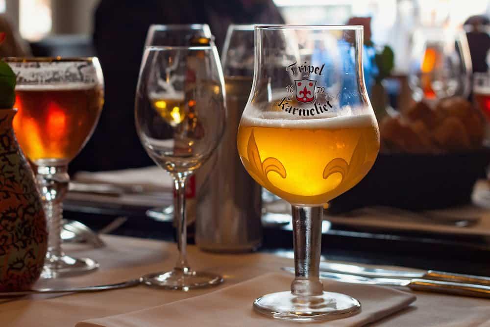 LEUVEN, BELGIUM - Original glass of Tripel Karmeliet beer in one of the restaurants in the Leuven. Is a golden Belgian beer with high alcohol by volume brewed by Brouwerij Bosteels