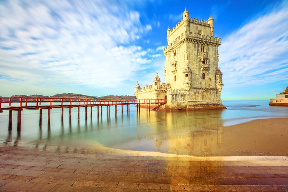 Scenic Belem Tower and wooden bridge miroring with low tides on Tagus River. Torre de Belem is Unesco Heritage and icon of Lisbon and the most visited attraction in Lisbon, Belem District, Portugal.