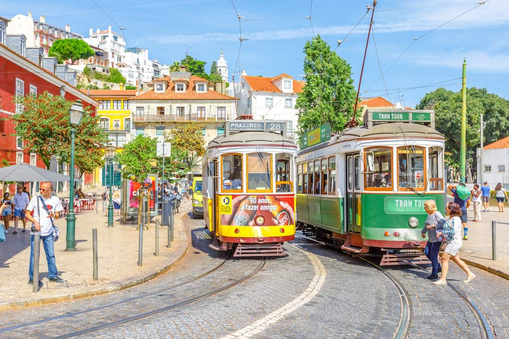 Lisbon, Portugal - new Tram Tour and famous vintage yellow Tram 28 near Portas do Sol viewpoint in historic Alfama District.Trams are icon of the Portuguese capital. Lisbon cityscape.