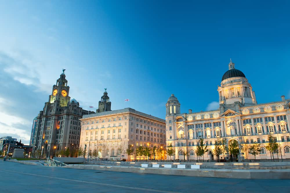 Liverpool city centre - Three Graces, buildings on Liverpool's waterfront at night, UK. Liverpool, in North West England, is a major city and metropolitan borough with population of 478,580 in 2015.