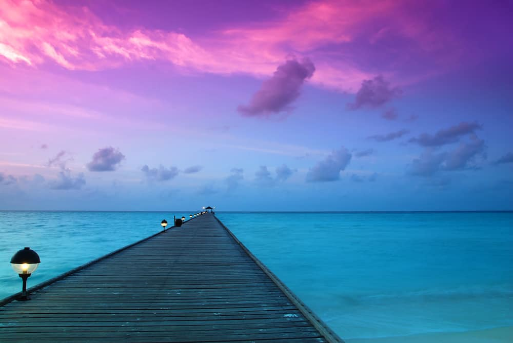 Beautiful sunrise over the sea and jetty in the Maldives Indian Ocean