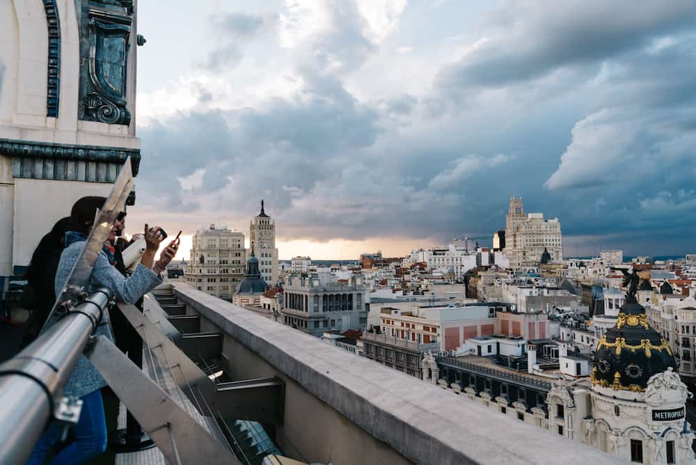 Madrid, Spain - People looking at skyline at rooftop on Circulo de Bellas Artes of Madrid at sunset.