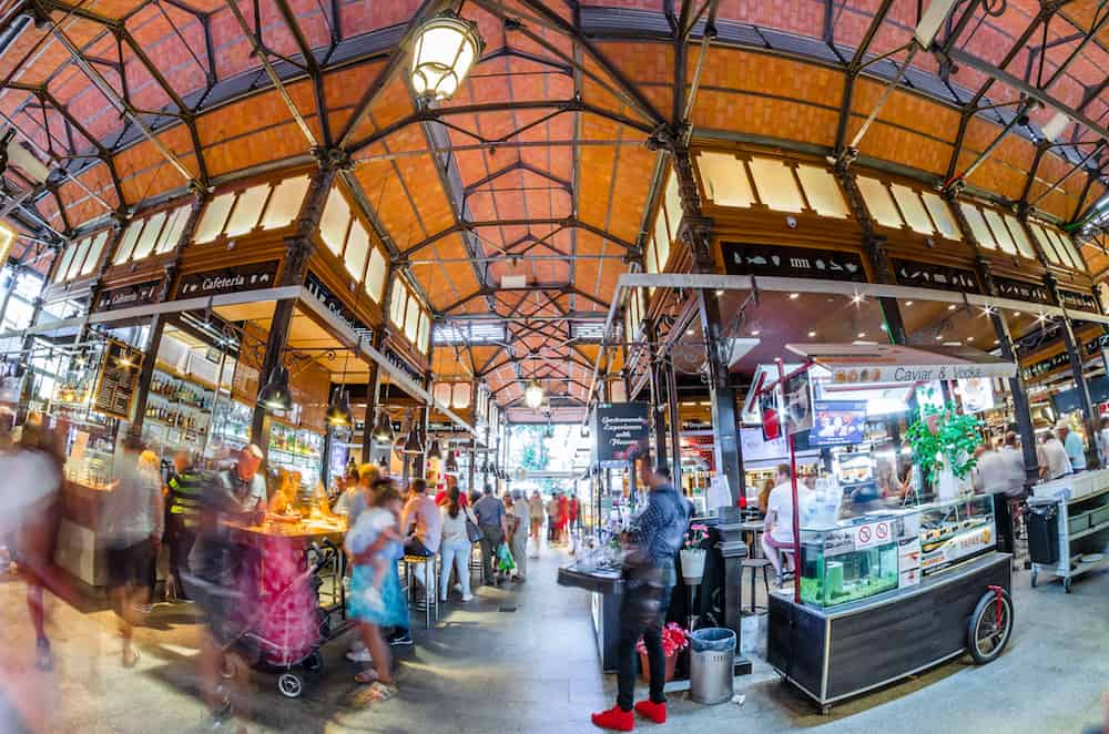 "MADRID, SPAIN -: People visiting and enjoying drinks and tapas inside the historical ""Mercado de San Miguel"" (Market of San Miguel), popular among tourists, located in the center of Madrid, Spain"