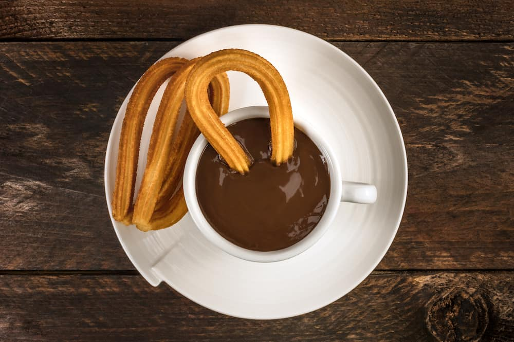 An overhead photo of churros, traditional Spanish, especially Madrid, dessert, particularly for Sunday breakfast, with a cup of hot chocolate